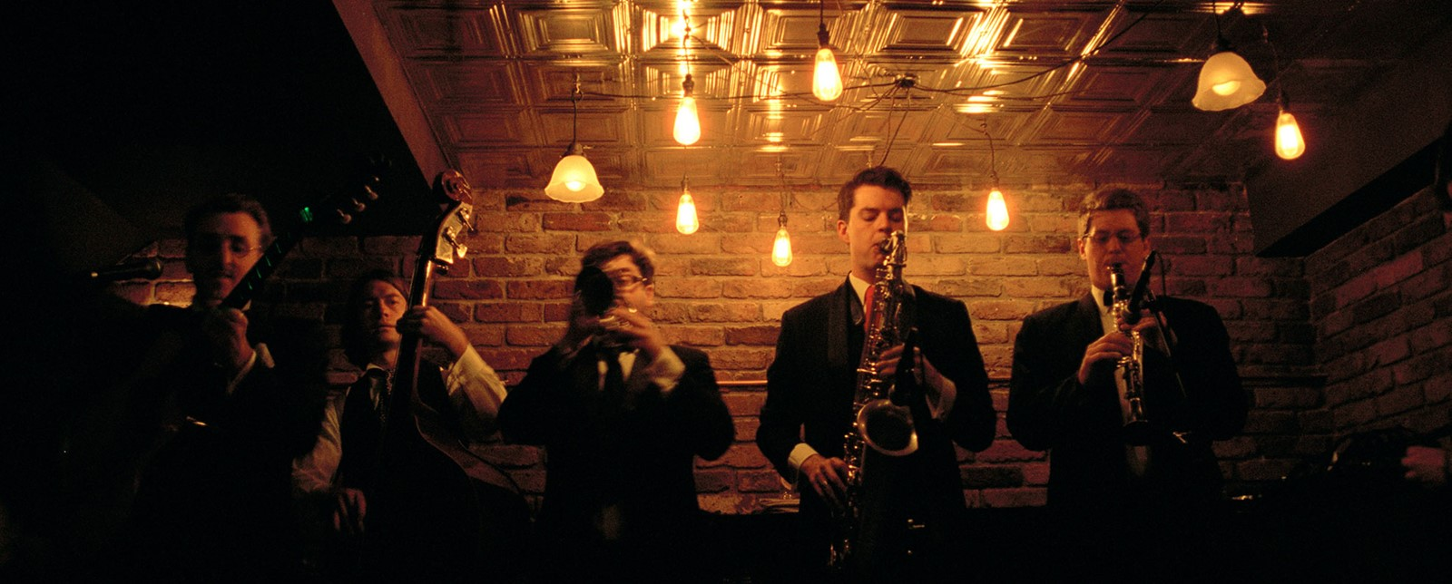 A horn section and double bassist playing at the Nightjar