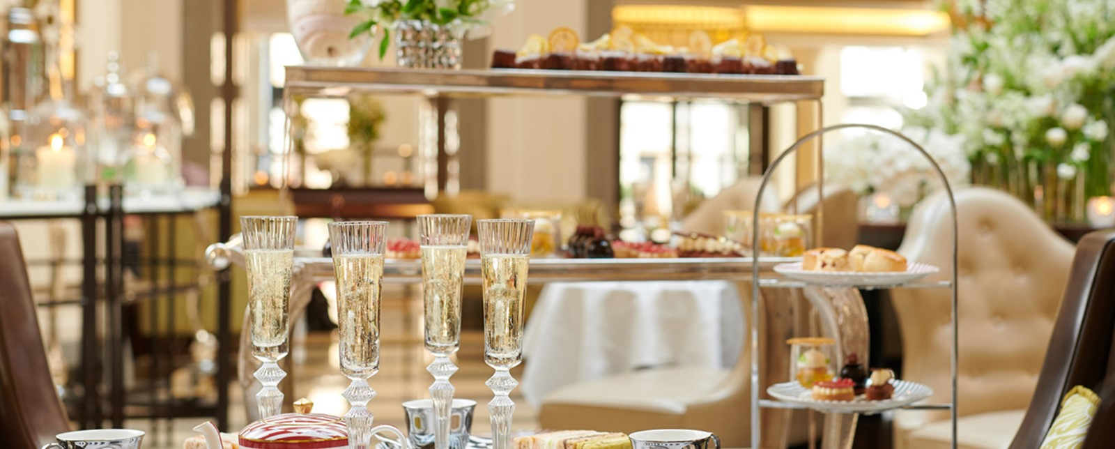 An afternoon tea spread of sandwiches, champagne, tea and desserts