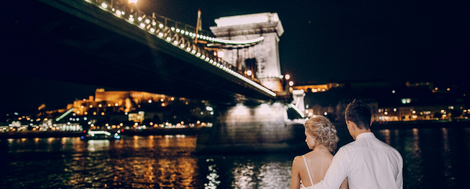 Couple sat by the riverbank in Budapest at night