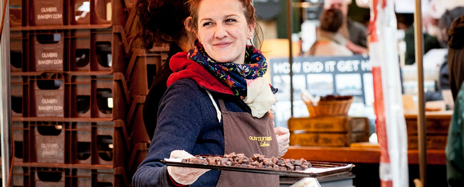 A smiling market trader holding a tray of sweets at Olivier's Bakery