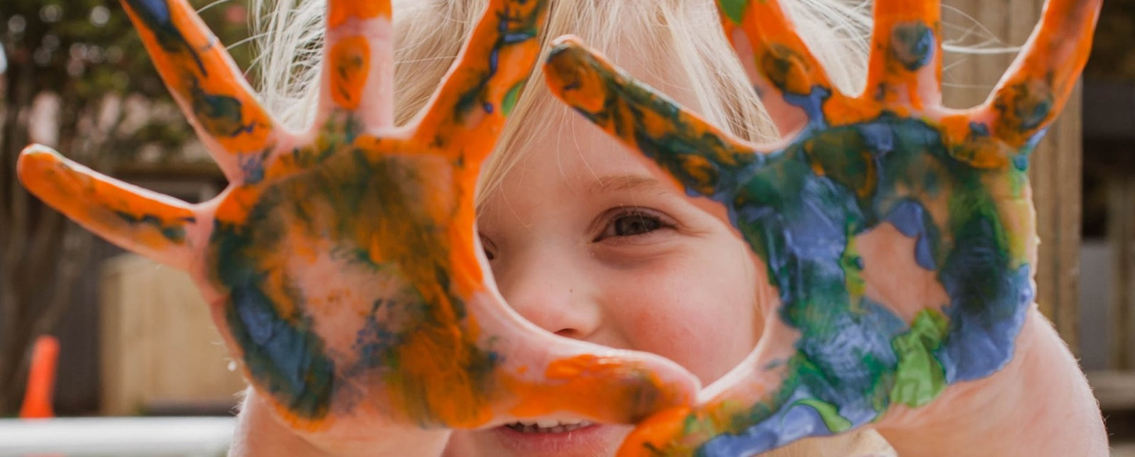 A girl holding paint stained hands in front of her face
